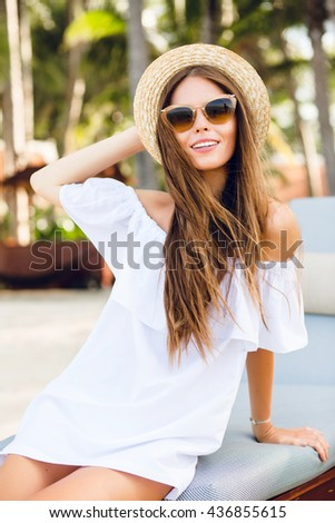 Cute girl in brown sunglasses and straw hat smiles charmingly. She wears  white short dress 5d00570a8d4