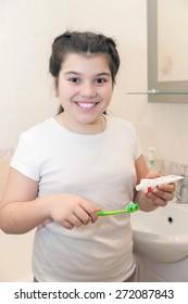 cute girl brushing her teeth in   bathroom.