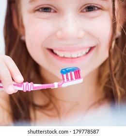Cute girl brushing teeth in bath close-up