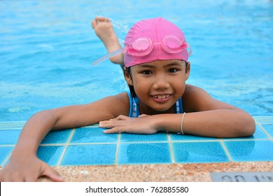 Cute girl burn calories by pool exercises. She exercise before swimming in the pool.