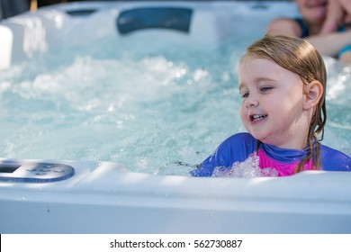 Cute girl caucasian toddler blonde hair blue eyes bright rash vest playing in water full of joy and happiness learning to swim and splashing about in the sun in the jacuzzi