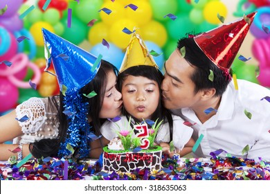 Cute girl celebrate birthday party and blowing the birthday candle with her parents