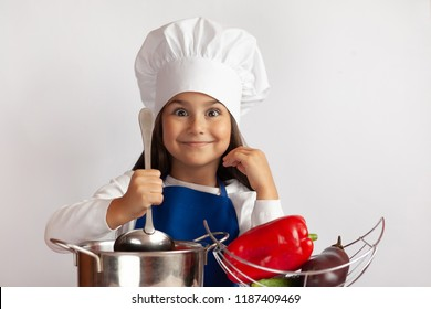 Cute girl in chef uniform cooking on light background. Child with fresh vegetables. Healthy food, healthy kids.