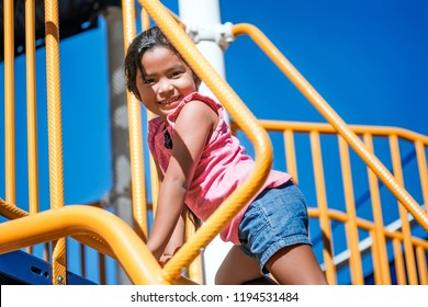 Cute girl climbing up a colorful kids playground using hands and feet with a smile on her face, displaying excellent motor skills
