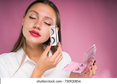 cute girl with closed eyes holding in her hands false eyelashes
