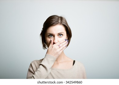 Cute girl closes her mouth with her hands, shocked, bright lifestyle photo, isolated on a gray background