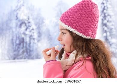 Cute girl clothes  applying lip balm