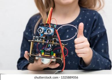 Ein süßes Mädchen sammelt elektronisches Roboterauto und programmiert es auf dem Computer. Die Boards und Mikrocontroller sind auf dem Tisch. STEM- und STEAM-Ausbildung. Programmierung. Mathematik. Wissenschaft. Technologie.