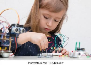 Ein süßes Mädchen baut einen Metallroboter und programmiert ihn. Die Boards und Mikrocontroller sind auf dem Tisch. STEM-Unterrichtsinschrift.Programmierung. Mathematik. Die Wissenschaft. Technologie. DIY.