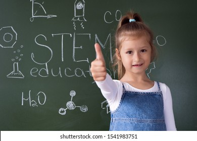 A cute girl constructs metal robot and program it on the computer. STEM education inscription. Programming. Mathematics. The science. Technologie. DIY.  STEAM. AI.