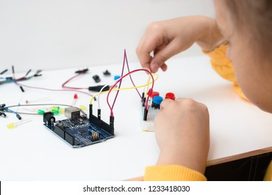 A cute girl constructs robot arduino and program it. The boards and microcontrollers are on the table. STEM education. Programming. Mathematics. The science. Technologie. DIY.