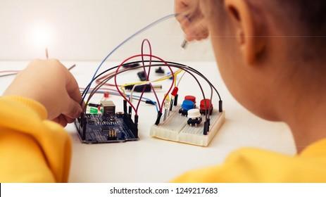 Ein süßes Mädchen baut Roboterarduino und programmiert es. Die Boards und Mikrocontroller sind auf dem Tisch. STEM-Unterrichtsinschrift. Programmierung. Mathematik. Die Wissenschaft. Technologie. DIY.