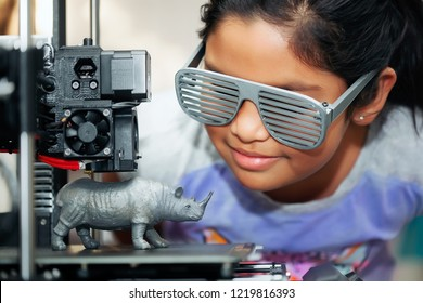 Cute girl with cool 3d printed shutter shades is watching her 3d printer as it prints her 3d model of a rhinoceros.