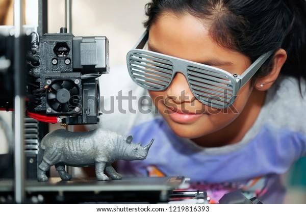 Cute Girl mit coolen 3D-Shuttertönen sieht ihren 3D-Drucker, der ihr 3D-Modell eines Rhinozeros druckt.