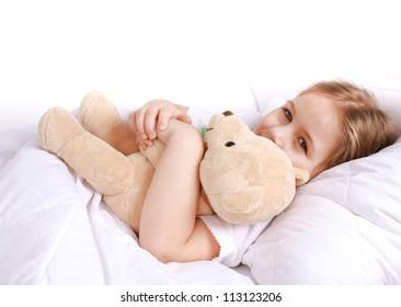 Cute girl cuddling with teddy bear to sleep