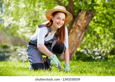 Cute girl cutting grass in the meadow