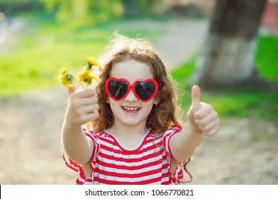 Cute girl with dandelion in her hand, showing thumbs up.