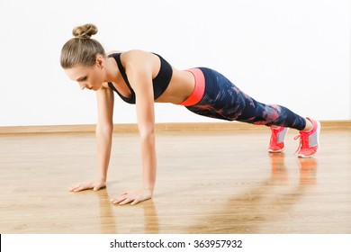 Cute girl with dark hair wearing pink snickers, dark leggings and black short top doing pushups at gym, fitness, white wall and wooden floor, copy space.