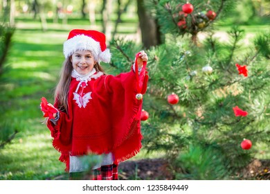 Cute girl decorating the Christmas tree outdoors in the yard before the holidays. Merry Christmas and happy holidays.