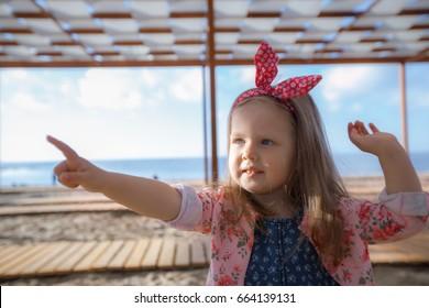 Cute girl in denim dress and pink shirt  at a beach