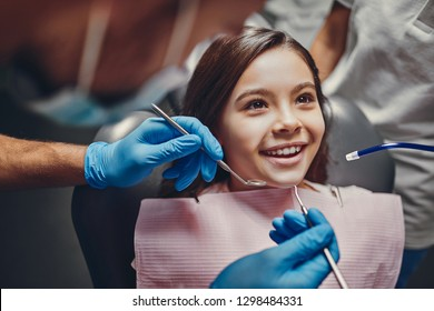 Cute girl in dental clinic. Child in stomatological cabinet with dentists.