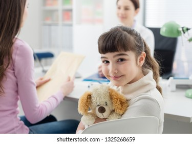 Cute girl in the doctor's office, she is hugging her teddy bear, children and healthcare concept