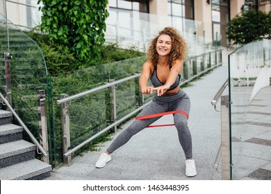 Cute girl doing fallout and  sits up on  gray wall on the stairs after morning jogging in the modern city. Morning concept.
