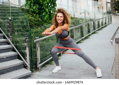 Cute girl doing fallout and  sits up on  gray wall on the stairs after morning jogging in the modern city.