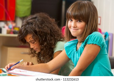 Cute girl doing homework with friend at home.