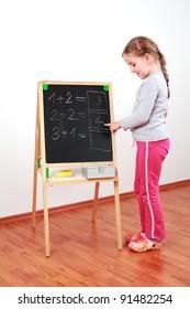Cute girl doing the math on chalkborard