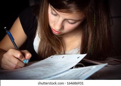 Cute girl doing school work in dramatic lighting