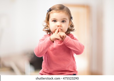 Cute girl doing silence gesture on unfocused background