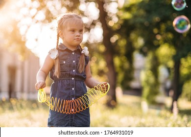 Cute girl with Down's syndrome playing outside, intellectual disability problem