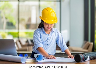 Cute girl dressed as an architect and working on a blueprint.