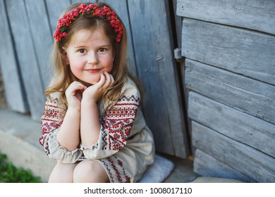 Cute girl dressed in embroidery play in the garden
