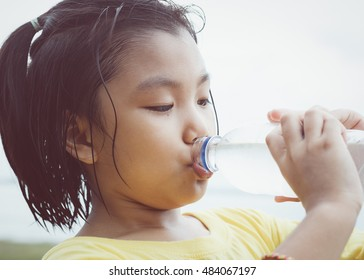 Cute girl is drinking water from plastic bottle. Clean water will help solve the thirst for her.
