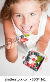 Cute girl eating fresh berries