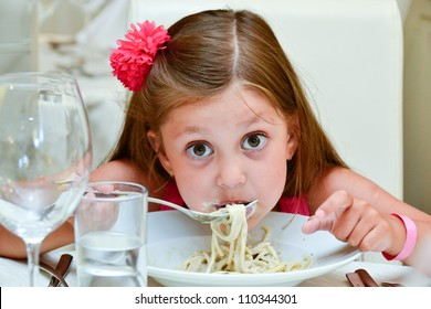 Cute girl eating pasta in Italian restaurant