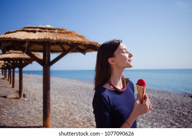 cute girl eating red ice cream on the beach, concept of summer sweet holiday.