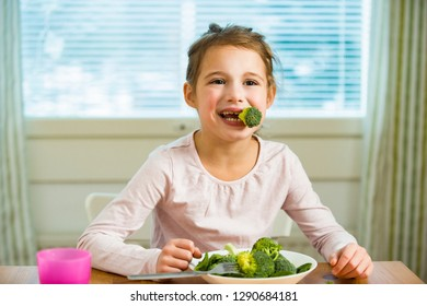 Cute girl eating spinach and broccoli at the table. Smiling and laughing happily. Healthy food concept.