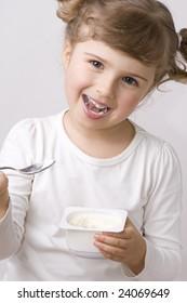 Cute  girl eating yogurt