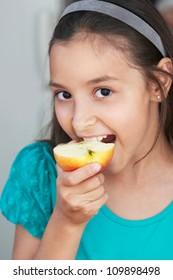 cute girl eats an red apple