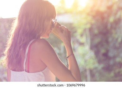 Cute girl enjoying morning coffee on the porch. Shallow depth of field on the cup.