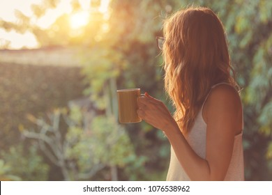 Cute girl enjoying morning coffee on the porch.