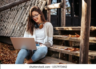 A cute girl with eyeglasses and wireless headphones is sitting on wooden stairs in front of a cabin and working on a laptop computer