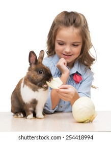 Cute girl feeding brown bunny with cabbage, isolated on white background