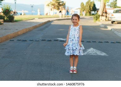cute girl in floral dress standing in middle of road