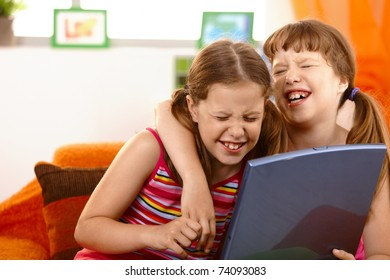 Cute girl friends laughing at laptop computer screen, hugging.