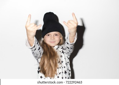 Cute girl gesturing rock at camera. Adorable girl showing devil's horns gesture and looking at camera.