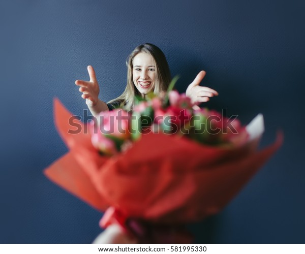 Cute girl getting bouquet of red tulips. Boyfriend giving tulips.